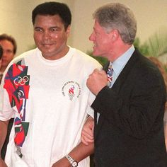 ATLANTA, GA - JULY 19:  US President Bill Clinton (R) takes the arm of boxing legend, Muhammad Ali at the opening ceremony of the centennial Olympic Games 19 July. Ali, ill with Parkinson's disease, accepted the Olympic torch on its final relay leg from J