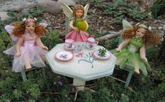 Three little fairies sit down for a tea party in our miniature fairy garden.