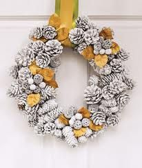 Image only (no instructions).  White dipped/painted pine cone wreath with gold accents.