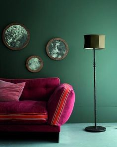 A deep pink sofa against a dark wall treatment. Ochre's eternal dreamer chaise, cast iron floor lamp and walnut framed with mercury glass mirrors