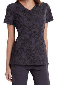 A stunning paisley print is the highlight of this fantastic top from the Careisma by Sofia Vergara collection!  You'll feel comfortable all day with the soft, stretch material from this modern fit top.  Front and back contour side panels will flatter your shape.  Two roomy pockets are included to tote your accessories.   Careisma By Sofia Vergara Pretty Little Paisley Print Scrub Tops  V-neck  Two angled pockets  Front and back side contour panels  Exterior logo charm  Side slits  Medium ...
