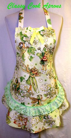 Girls apron in an adorable designer screen print entitled Morning Flower Fairies, with the cutest little winged creatures in 12 shades of green on an ivory background. If you look closely, you can even see the Fairy Dust in their hair and wings. Trimmed with pistachio green eyelet lace above the feminine ruffled flounce and a pretty satin bow.  We love making kids aprons. Do you know a little girl who would love to help you cook dressed in this lovely mini apron? Sure you do! $27.50