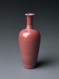 "Lush pinkish-red glazes, such as the ""peach bloom"" on this small vase, were first produced in the third quarter of the seventeenth century. Small vases in this shape have long been thought to belong to sets of eight or more accoutrements designed for a writing table"