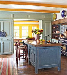 A wooden cabinet that once stored tools in a factory now serves as an island in this colorful country kitchen. Complete with an old cast-iron sink, the island boasts a pretty blue hue that mixes with pale green cabinetry and yellow trimwork in the adjacent dining room.