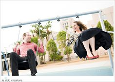 Fun playful engagement photos by la vida creations with couple playing on swings in downtown playground. Photos by La Vida Creations Photography.