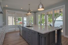 Kitchen: natural maple hardwood floors, quartzite counters, painted cabinets, contrasting painted island cabinets with pillars, stainless steel appliances, lake views and natural light.