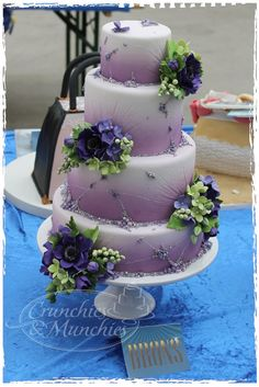 Purple and white frosting but with blue hydrangea decor on top of each layer