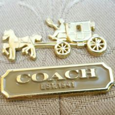 Coach Signature Evening Gold Coach Evening bag. VERY GENTLY UTILIZED. Signature horse & carriage plaque @ front center. Top zip close brown sparkly leather brown toggle which matches leather shoulder strap gold tone hardware Signature gold tone large buttons @ either end. Clean plum satin interior. SEE PICS FOR EVERY BEAUTIFUL DETAIL! This is a night and day staple to be worn while you are dressed up or down! A unique piece that is affordable luxury. L10 H6.5 5DROP. Coach Bags Hobos