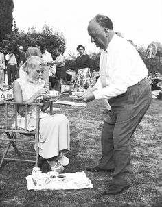 """Alfred Hitchcock serves tea to Grace Kelly on the set of """"Dial M For Murder"""" 1954"""