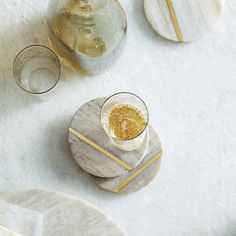 Designed here in California, this gorgeous set of smooth almond and grey toned marble coasters are intricately accented with a single stripe of satin brass. Details - Comes as a set of 4 coasters - Ma