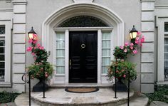 This home features circular stone steps leading toward a detailed black door with hexagonal brass knocker at center. The large arched doorway and windows frame the door in brighter tones. Arch Doorway, Front Entry, Entry Doors, Front Porch, Stone Steps, Victorian Front Doors, Home Appraisal, Front Courtyard, Black Front Doors