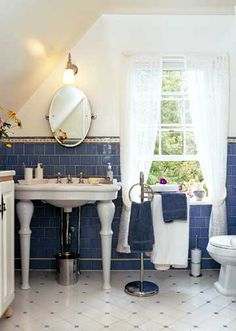 White bathroom with blue tiles partially up the wall