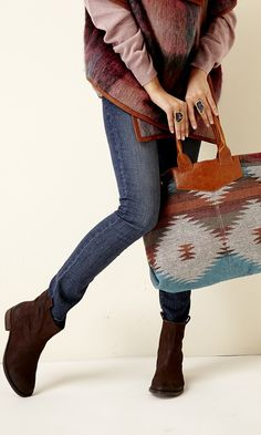 A Southwestern-printed fabric tote with a roomy interior, faux leather trip, top handles and removable crossbody straps.