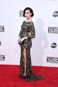 Demi Lovato stuns on the 2015 American Music Awards red carpet in a black lace gown with a thigh-high slit.