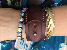 """There's nothing quite like Plunder Design Arm Candy- pictured here you see our Pippa Cuff ($16This sexy leather cuff goes with everything. 7.5"""" to 8.5"""" adj.) Dixie Bracelet ($18 Triangle pattern gold bracelet. 8.5"""" Stretch elastic.) and Flynn Bangle ($26 Antique bronze surrounds these iridescent gems. Magnetic closure 9"""")"""