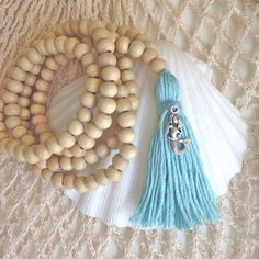 beachcomber tassel necklace  natural wood beads with an aqua cotton tassel with silver mermaid charm, all handmade by me.  length from top to