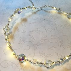 Your eyes aren't playing tricks on you... this necklace really does light up! Tiny LED twinkle lights are woven into the wirework, and a lightweight battery pac