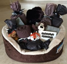 """New Puppy"" gift basket. Dog bed stuffed with gifts...Tiger Dreamz faux fur pet sleeping bag/blanket. Fleece pet blanket. Stuffed Toys. squeaky balls. Potty pads. Electric pet bed heater. Petco gift card. Cash for vaccinations."
