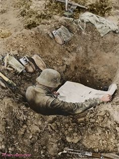 German soldier reading a newspaper in his foxhole on the Eastern Front. 1941.