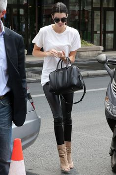 In Paris wearing a white t-shirt and black leather pants with a Givenchy handbag.   - HarpersBAZAAR.com