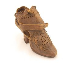 Shoe of perforated brown leather. High heeled shoe with high fanned tongue, fastened by a strap. Probably a shoe apprentice's model made to demonstrate his skills and possibly for display purposes to advertise the range of good or skills on offer at the shoemaker's. Europe. Date: 1714-1730 #shoes #fashion