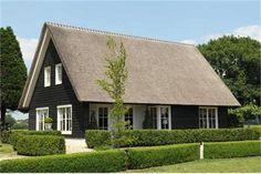 Zwart houten huis met rieten dak