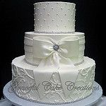 Elegant White Butter Cream Wedding Cake with Fondant Sash and Bow by Graceful Cake Creations