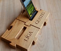 Personalized Wooden Mobile Phone Stand Custom by KlikKlakBlocksPersonalized wooden mobile phone stand. This custom iPhone dock is made of natural oak. It will be a perfect custom rustic cell phone holder and it will make a wonderful gift on anniversary, Valentine's Day, birthday or any other occasion. It is made in a shape of a wooden puzzle so that you can combine more than 1 pieces of these phone docks together.  More: www.etsy.com/shop/KlikKlakBlocks
