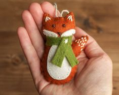 This little red fox is bundled up in her green scarf and looking for a cozy place to call home. Her playful nature is perfectly suited for a woodland-themed childs room, your Christmas tree, or as a gift for any child at heart with a soft spot for our furry forest friends.  This friendly fox ornament was designed and hand cut by me using high quality wool blend felt. I then carefully stitched and embroidered her by hand. She is filled with wool and hangs from a loop of hemp twine.  This…