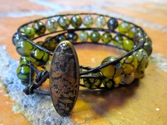 Burnished bronze oval button and green cat-eye beads on a double wrap black leather bracelet