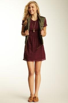 I absolutely adore the burgundy patern texture dress with the olive army vest over it. Gold necklaces, blone curly hair, and oxfords nice touch.