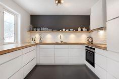 Mano Keuken van Kvik. Door de combinatie van de belijning, het wit, hout en de donkere kleuren, geeft de keuken rust, maar toch sfeer. Kvik; Keukens, badkamers en garderobe kasten.
