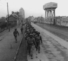 Black Soldiers on the march in Noyon (France) on their way into Germany. WWII.