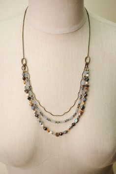 A collage of gemstones in this handmade vintage-style multi strand necklace include crystal, pearl, and abalone with mixed antique brass metals. Antique brass chain and components (nickel and lead-saf