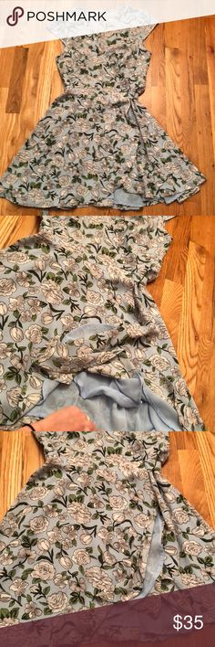 """Anthropologie Flower Wrap Dress Anthropologie Baby Blue Wrap Dress w/ White, Gray and Green Flowers. Adorable cap sleeves, ruffles with a peek a boo baby blue liner. Adjustable tie waist for a perfect fit. Excellent condition, zero flaws!! Size Small. Length 34"""" Anthropologie Dresses"""