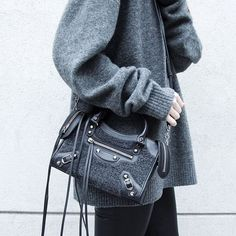 Oversized cashmere pullover and Balenciaga bag in grey.