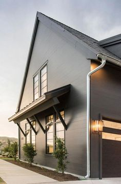 examples of black house paint to update and modernize a home exterior along with wood and stone accents, white trim, and landscaping for curb appeal Black House Exterior, Grey Exterior, Modern Farmhouse Exterior, Exterior Paint Colors, Exterior House Colors, Exterior Design, Farmhouse Style, Industrial Farmhouse, Black Windows Exterior