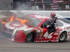 Kyle Larson exits his car after it caught fire following