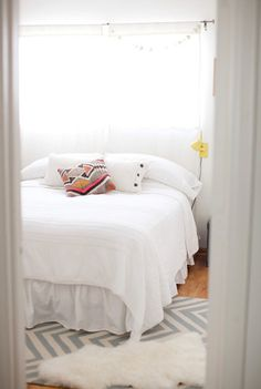 eclectic bedroom by Annie McElwain Photography.. Small room, but the white linens give a really open, airy feel.