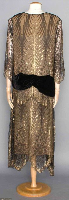 "GOLD & BLACK LACE EVENING GOWN, c. 1922. Lace & lame in frond pattern, black velvet hip sash, long sleeves, V-neck, handkerchief hem, H 40"", L 51"", (few breaks in chiffon backing) excellent; t/w 1 c. 1925 lame & velvet party dress, patterned lame bodice in tropical foliage pattern, black silk velvet sleeves & flared skirt. Back:"
