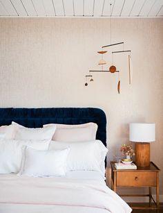 rose gold wallpaper with navy velvet headboard | Emily Henderson