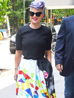 Kelly Osbourne paired black dramatic cat-eye sunnies and a matching top with a vibrantly patterned skirt for a pop of neon color!
