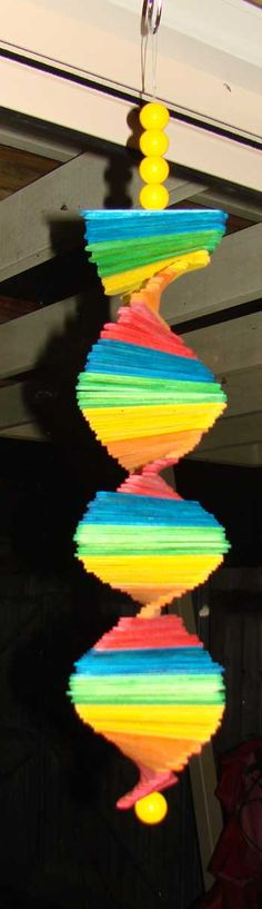 ☆ Make A Rainbow Wind Mobile ☆ (Summer craft ideas for kids don't get any cooler than this wild and vibrant decorative craft. Hang this outside on your porch, or bring the fun inside by dangling this summer craft for kids in their room. This is the perfect craft for kids to make since it's made with inexpensive Popsicle sticks.)