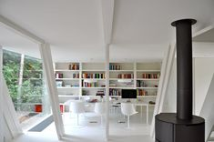 Extension vB4 by dmvA white walls; wall to wall bookshelves; black stove; glass;