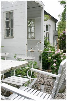 A side garden with freshly painted white wood & iron outdoor chairs at Sage Farm. The perfect setting for morning coffee & light lunches prepared by Chef 'Sage' Duchamps.