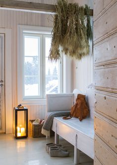 Cozy, rustic entryway lounge created by enclosing part of a two-level porch. The house is on an old reindeer farm near Tiimisjärvi in Finland.