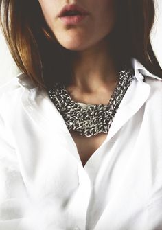 Crisp white shirt and chain necklace.