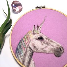This majestic needle felted unicorn is a one of a kind wool painting. This needle felted unicorn is on lavender wool felt, set in a 7-inch natural bamboo embroidery hoop.   SPECIFICS:  -Needle felting or wool painting is a method of using a barbed needle to felt together wool fibers onto a flat wool felt surface. I spend hours on each piece, meticulously layering different colors of wool to create a unique work of art.  -There is no glue or thread holding this together; the fibers…