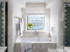 Onyx slabs and polished nickel trim on sandblasted glass doors add distinction to this master bath.