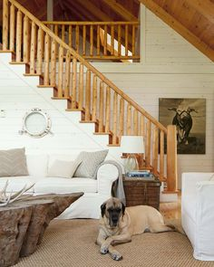 Relax Inside a Calming Ohio Lake House. Baby, a rescue dog, presides over the open-plan living area, where an old porthole frame adds interest to the white walls. Ohio, Frame Layout, Oak Trim, Pleasant Hill, Neutral Paint Colors, Lake Cabins, Living Room Carpet, Living Rooms, Mud Rooms